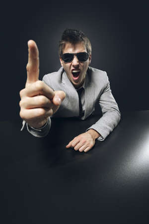 angry businessman: Young angry businessman boss is pointing his finger and screaming Stock Photo