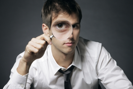 businessman looking through a magnifying glass Stock Photo - 15783267