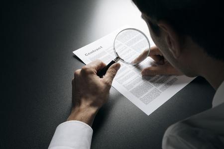 lupa: Joven hombre de negocios en busca de un contrato a trav�s de una lupa Foto de archivo