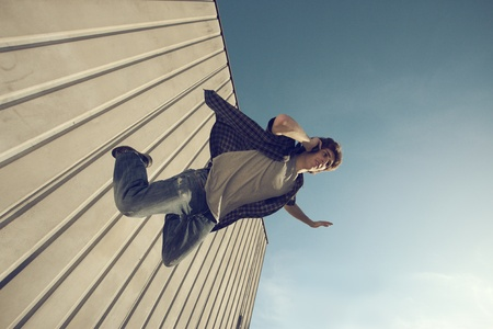 Young man is falling from a building and calling with cell phone photo