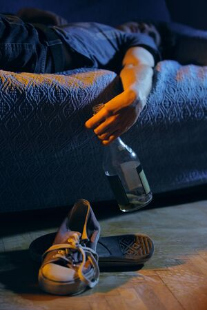 alcohol abuse: Young drunk man, lying on the couch with a bottle in hand