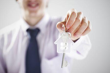 Klucze: Młody biznesmen dając klucze do domu