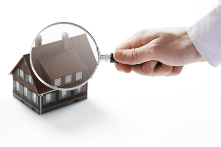house inspection: Concept image of a home inspection. A male hand holds a magnifying glass over a miniature house.