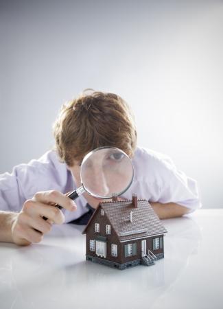 housing search: Giovane che tiene una lente di ingrandimento su una casa in miniatura. Archivio Fotografico