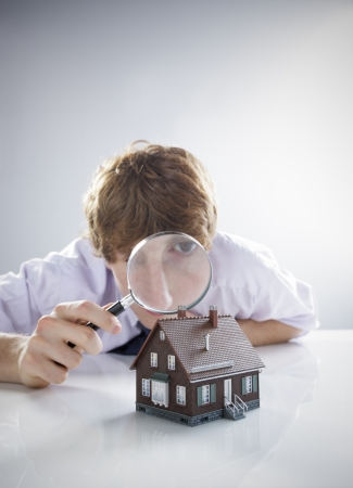housing problems: Young man holds a magnifying glass over a miniature house.