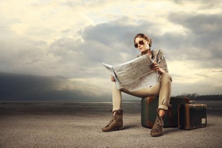 Piękna młoda kobieta siedzi na walizkach