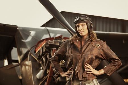 piloto: Retrato de mujer joven piloto de avión. Avión en el fondo