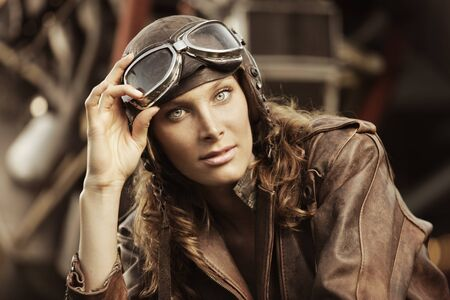Portrait of young woman airplane pilot. Airplane on the background Stock Photo - 16141172