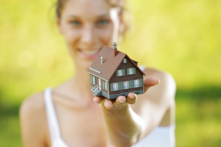 Young beautiful woman offering a house photo