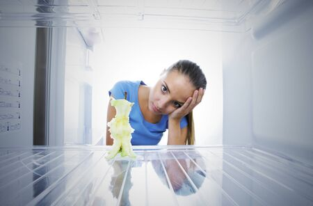 Young woman unhappy to see the empty fridge photo