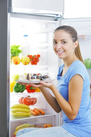 refrigerator with food: Beautiful young woman sitting near refrigerator  and choosing between healthy fruits and tasty cakes Stock Photo