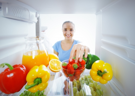 refrigerator with food: Woman reaching for food in refrigerator, view from inside