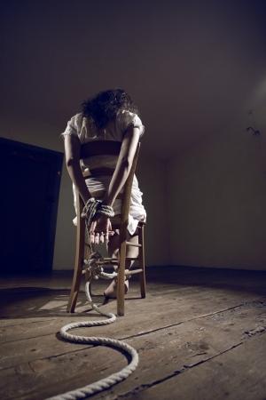 gefesselt: Junge Frau auf einem Stuhl in einem leeren Raum gebunden Lizenzfreie Bilder