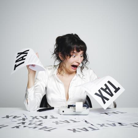 impuestos: Mujer muy sorprendida de su escritorio mirando las facturas de impuestos terribles