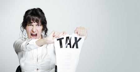 Young desperate woman at her paperwork-covered desk ripping up a tax form staring at the camera Stock Photo - 16141315