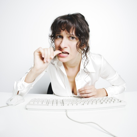 frontal portrait of a doubtful woman nail biting at her office desk Stock Photo - 16141296