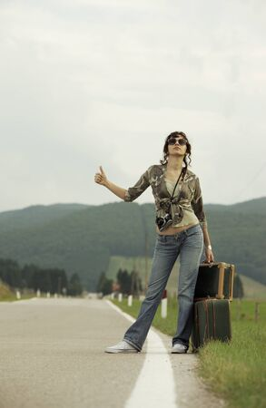 runaway: A woman hitchhikes on the side of the road.