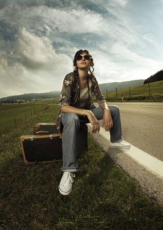 atop: Girl in the road sit atop vintage suitcase Stock Photo
