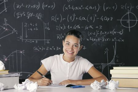 Young student writes in the notebook, in the background a blackboard full of math formulas photo