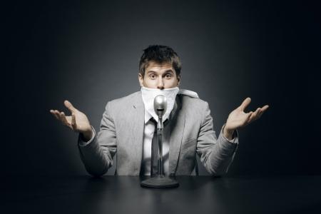 imbavagliare: Giovane uomo d'affari con il bavaglio censura suo mese