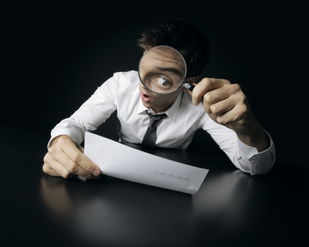 myopic: Young businessman looking to a contract through a magnifying glass  Stock Photo