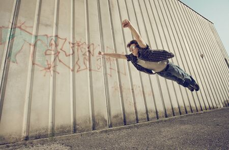 flying man: A young man feels like a superhero, flying free. Stock Photo