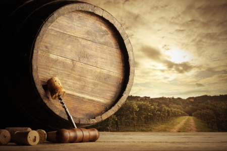 corkscrew and wooden barrel, vineyard on background photo