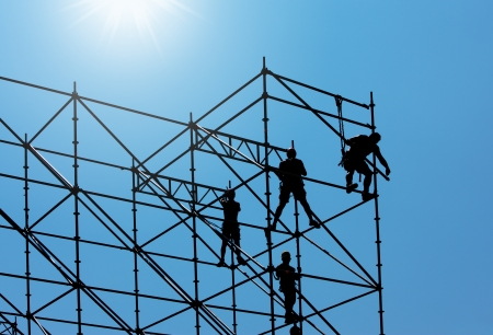 andamios: Silueta de trabajadores de la construcci�n en un andamio trabajando bajo un cielo azul