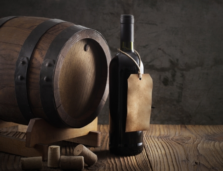 vintage bottle: Wine bottle with barrel and old paper label Stock Photo