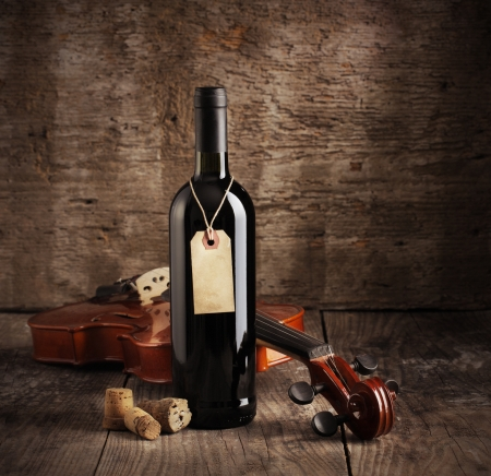 Red wine bottle and violin on wooden background