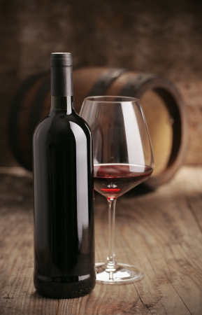 merlot: Wine bottle with glass,  barrel on background Stock Photo