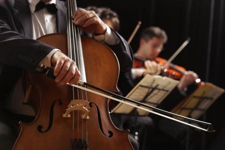 Koncert symfoniczny, mężczyzna gra na wiolonczeli, ręcznie zamknąć