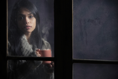 Woman behind window with a cup of coffee or tea, focus on hand photo