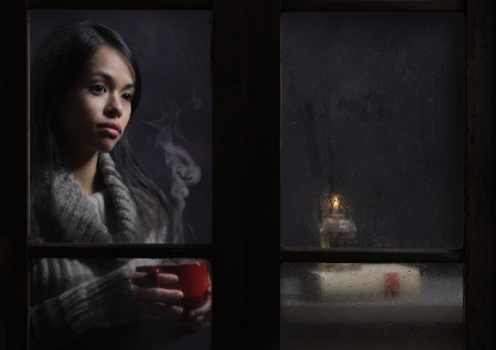 Woman behind wet window with a cup of coffee or tea photo