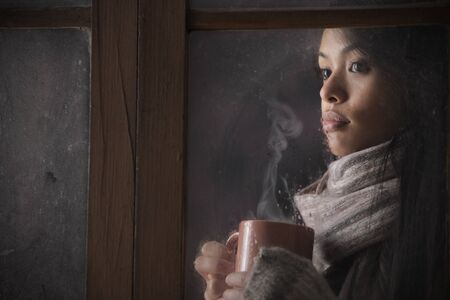 Portrait of a beautiful woman behind window with a cup of coffee or tea photo