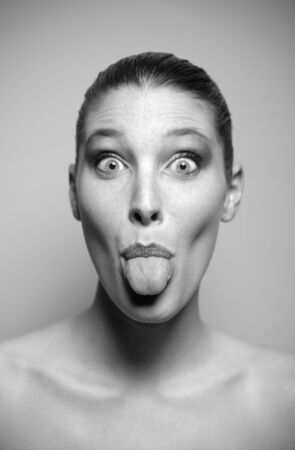 Young beautiful woman pokes out her tongue photo
