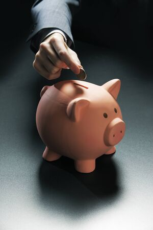 Businessman hand putting coin into a piggy bank photo