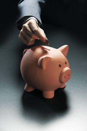 Businessman hand putting coin into a piggy bank Stock Photo - 16675917