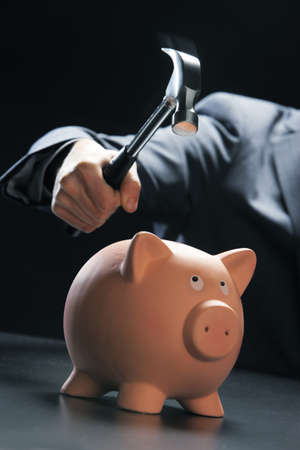 Hammer about to smash piggy bank, focus on hammer head Stock Photo - 16675914