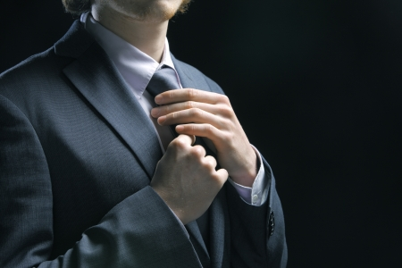and the horizontal man: Well dressed business man adjusting his neck tie
