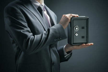 Businessman protecting his savings in the safe Stock Photo - 16675913