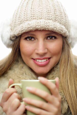 ropa de invierno: Joven mujer llevaba ropa de invierno con una bebida caliente