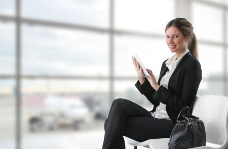file d attente: Portrait de jeune femme d'affaires travaillant sur tablette num�rique � l'a�roport