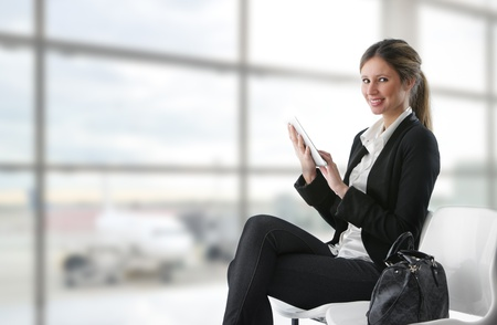 business travel: Portrait of young business woman working on digital tablet at airport