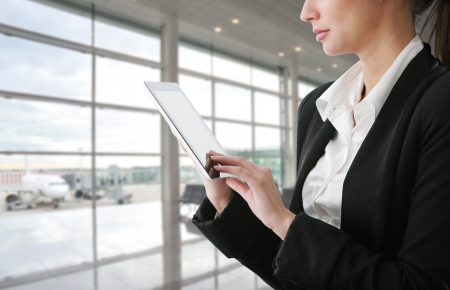 business airport: Businesswoman using tablet computer at departure lounge