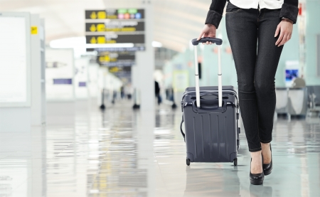 Jonge vrouw die bagage op de luchthaven, close-up sexy benen