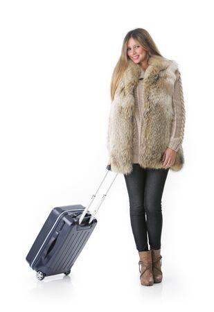 ropa de invierno: Mujer joven en ropa de invierno con una maleta con ruedas.