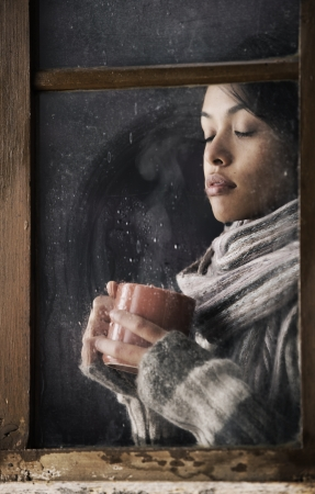 Portrait of a beautiful girl behind window with a cup of coffee or tea photo