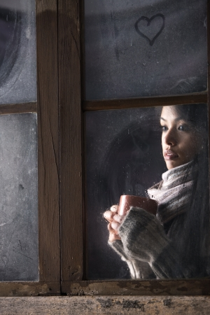 Portrait of a beautiful girl behind window with a cup of coffee or tea Stock Photo - 17053975