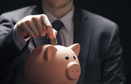 Businessman hand putting coin into a piggy bank Stock Photo - 17070672
